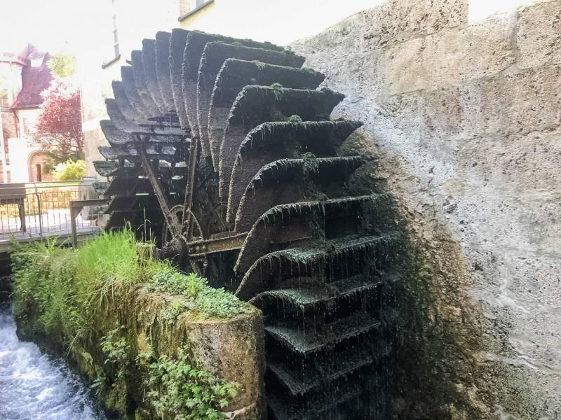 Altes, von Moos bedecktem Wasserrad, das noch immer Wasser befördert.