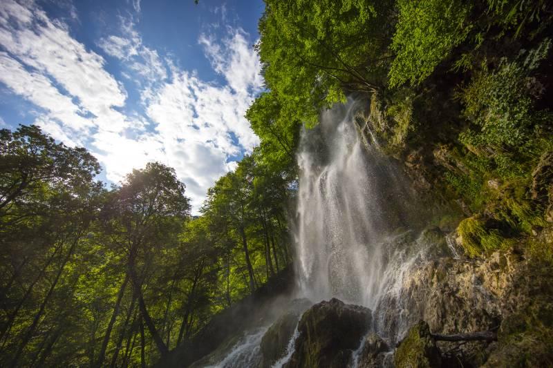 Bad Uracher Wasserfall, Wasser stürzt in die Tiefe, im Hintergrund sind Bäume und ein Stück blauer Himmel mit weißen Wolken
